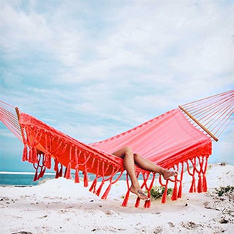 Remington girl laying in hammock on beach