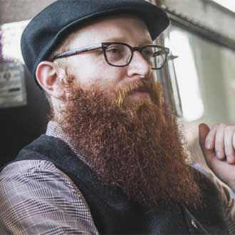 remington instagram man with big red beard and glasses looking to the side
