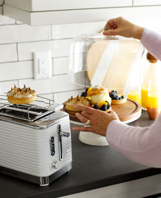 Russell Hobbs White 2-Slice Coventry Toaster with woman warming pastries